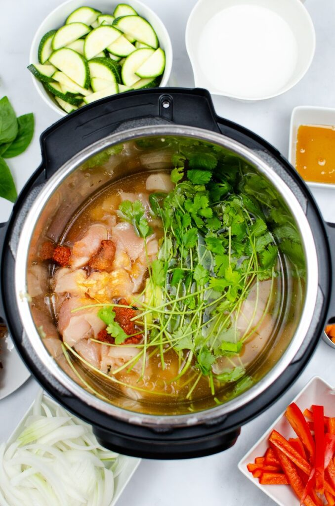 Instant Pot Thai Red Chicken Curry in an instant pot with additional ingredients in bowls around the pot