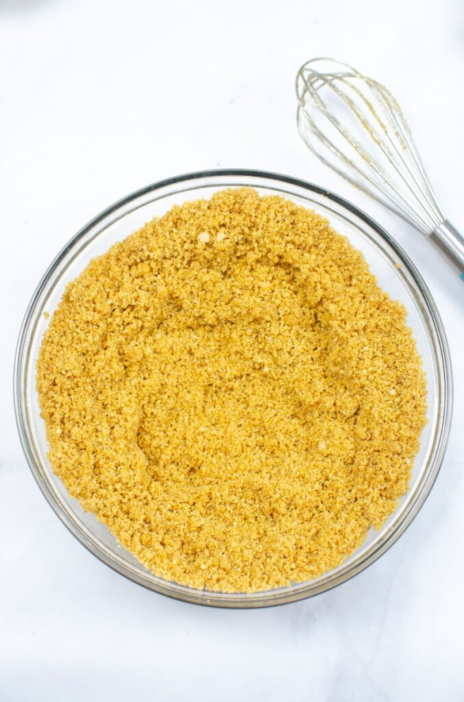 Graham cracker crumbs in a glass bowl next to a whisk.