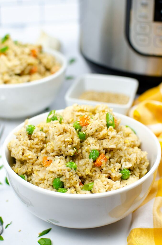 Chicken fried rice in a white bowl next to an instant pot.