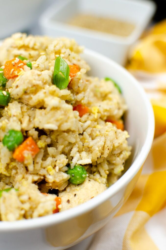 close up of Instant pot chicken fried rice in white bowl.