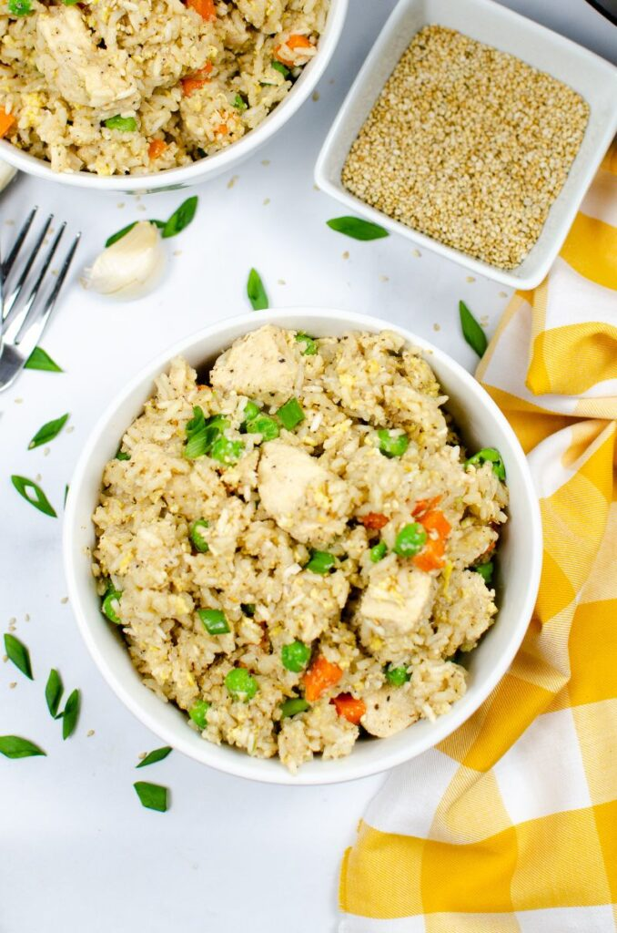 Instant pot Chicken Fried rice in white bowls sprinkled with green onions.