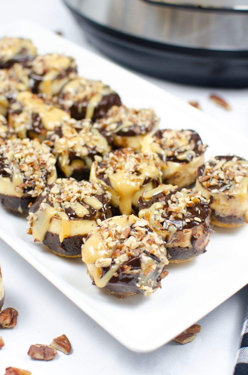 A twist on the regular turtle candy, these Instant Pot Mini Turtle Cheesecakes have a graham cracker crust and creamy cheesecake based. Topped with lush caramel, rich chocolate ganache, and crushed pecans, they ooze deliciousness with every bite! #turtlecheesecake #instantpot #instantpotcheesecake #turtlecheesecake #howtomakecheesecake #cheesecakebites #homemadecheesecake #pecandesserts #homemadedesserts #minicheesecakes #cheesecake #grahamcrackercrust #cheesecakebites #easydesserts via @wondermomwannab