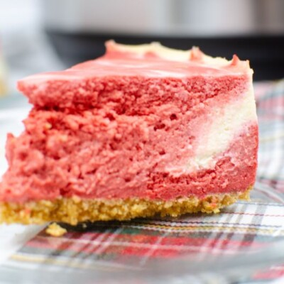 Slice of red velvet cheesecake on a glass plate.