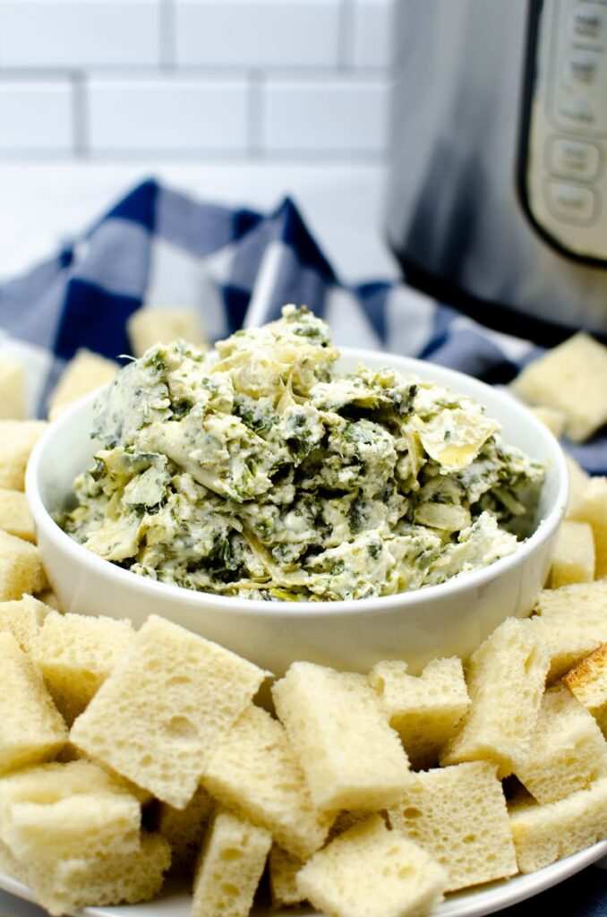 A white bowl of spinach artichoke dip on top of a white plate of bread cubes near an instant pot.