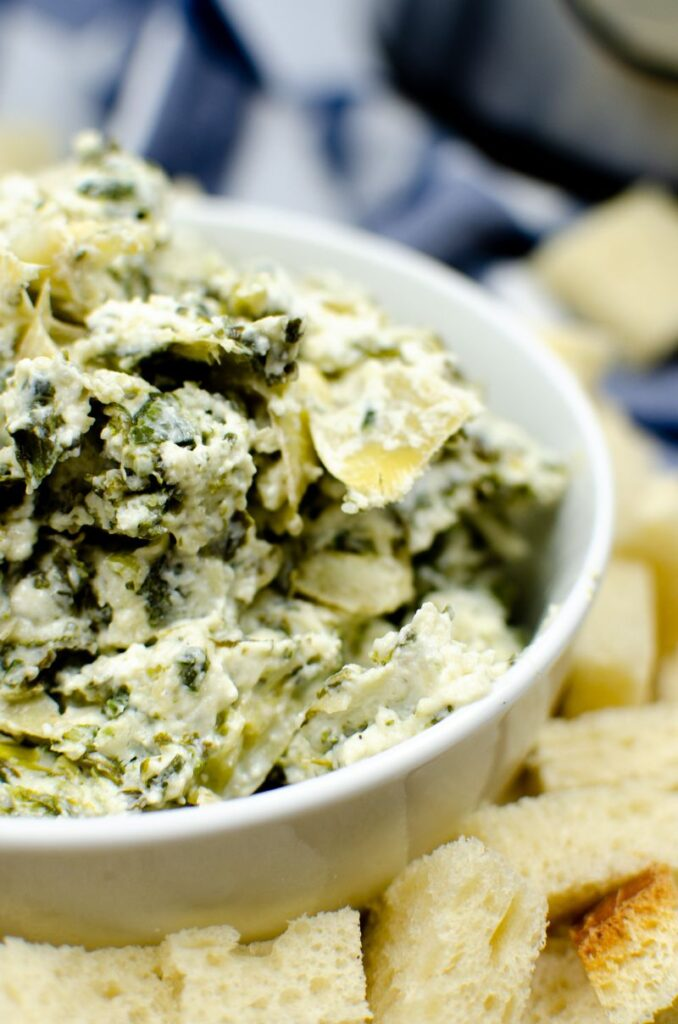 A white bowl of spinach artichoke dip placed on top of bread cubes.