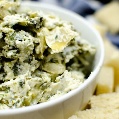 A white bowl of spinach artichoke dip in another white bowl of bread cubes.
