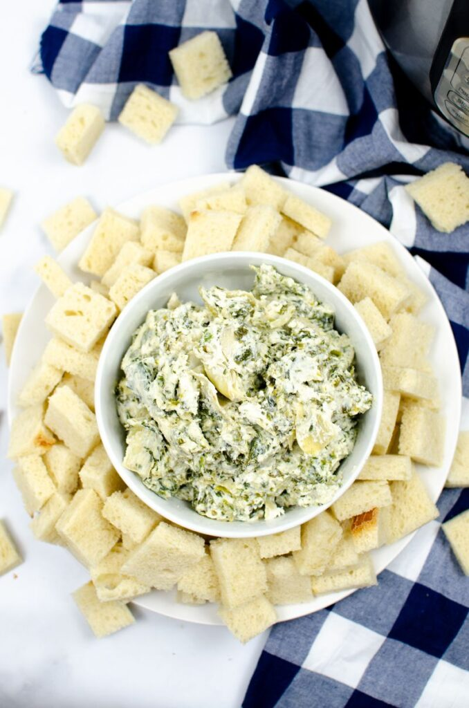 A white bowl of spinach artichoke dip on top of a white plate of bread cubes.