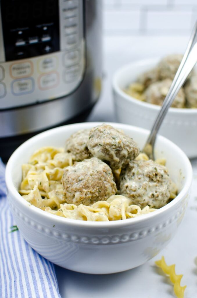 Meatballs and pasta in white bowls in front of an instant pot.