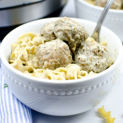 Swedish meatballs and pasta in a white bowl in front of an instant pot.