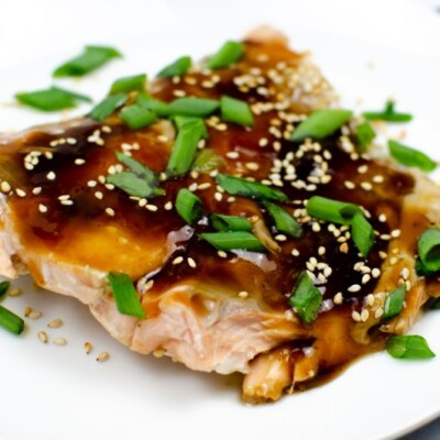 Baked salmon in Teriyaki Sauce on a white plate garnished with sesame seeds and green onions.