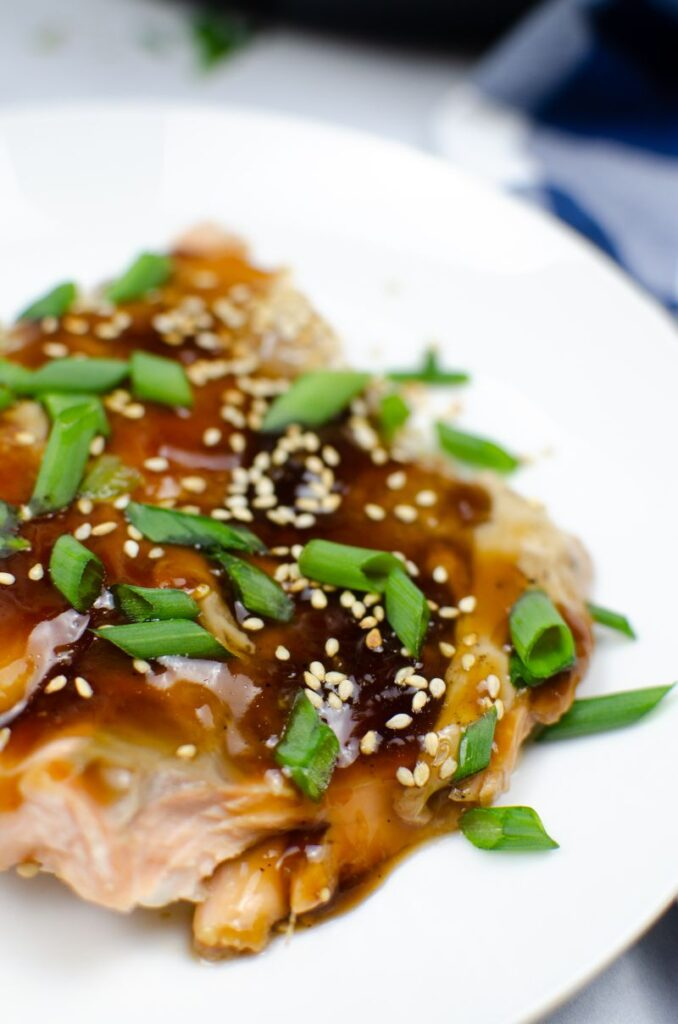 Large slice of baked salmon in Teriyaki Sauce on a white plate garnished with green onions and sesame.