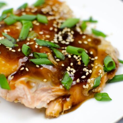 Slice of baked salmon in Teriyaki sauce covered with sesame seeds and green onions on a white plate.