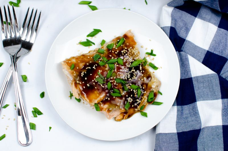 Top view of Teriyaki Salmon in a white plate next to two forks.