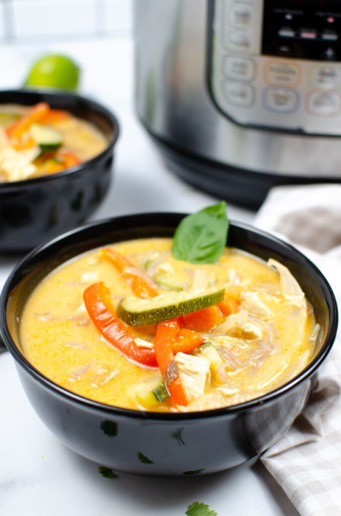 Instant Pot Thai Red Chicken Curry in a black bowl with another bowl of soup and an instant pot in the background