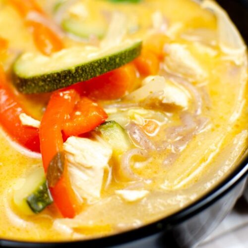 Thai red chicken curry in a black bowl with red peppers and zucchini on top.