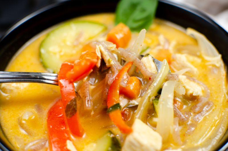 Instant Pot Thai Red Chicken Curry in a black bowl with a spoonful of soup above it