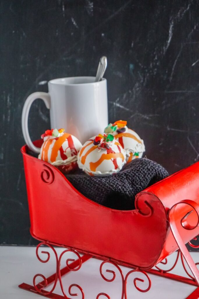 Old Fashioned Candy Hot Cocoa Bombs  in sleigh with white mug