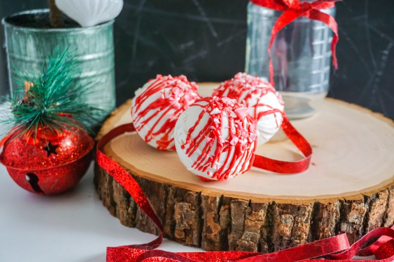Peppermint Hot Cocoa Bombs on wooden platter  next to a glass jar with a red ribbon on it, a tin can, and a red decoration