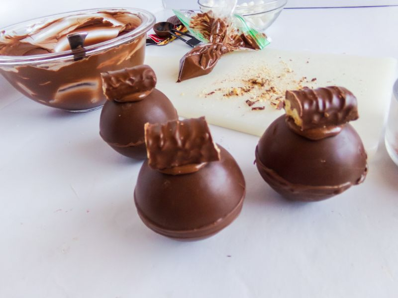 cocoa bombs topped with melted chocolate and a piece of a twix bar