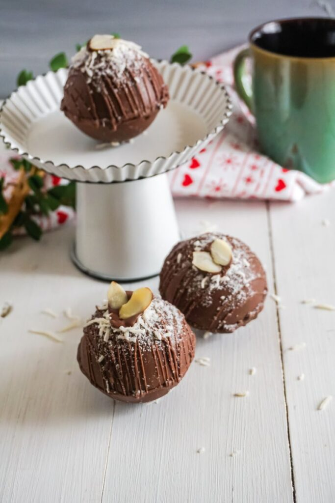 almond joy hot cocoa bombs  on platter with a green mug in the background