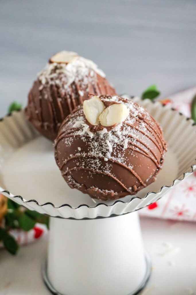two almond joy hot cocoa bombs on white cake stand
