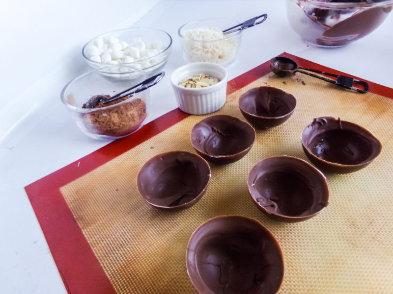 hot cocoa bomb molds on a baking mat next to bowls of the filling ingredients