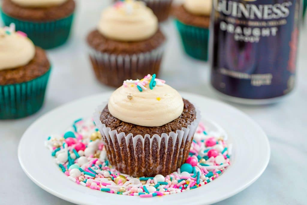 Chocolate Stout Cupcakes with Irish Whiskey Filling surrounded by sprinkles on a white plate with a can of alcohol and more cupcakes in the background