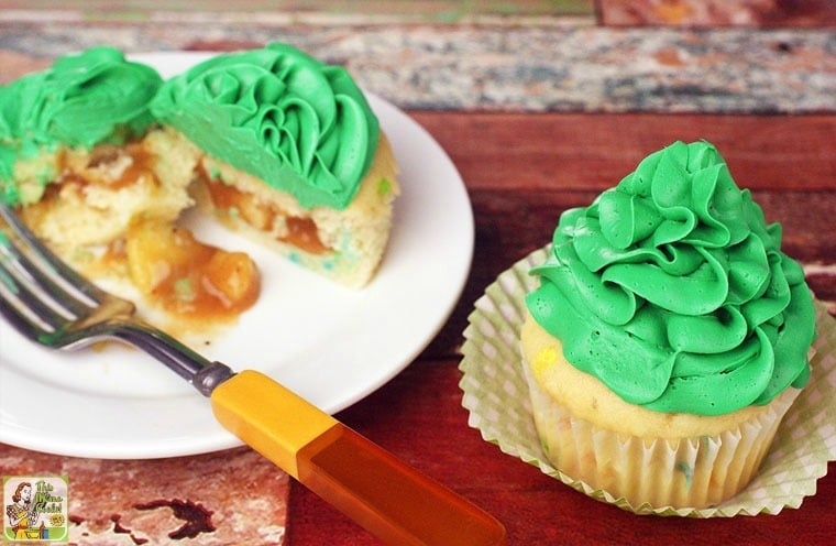 St. Patrick's Day Gold Filled Cupcakes, one cup open on a plate to show the inside and another whole one in a cupcake liner