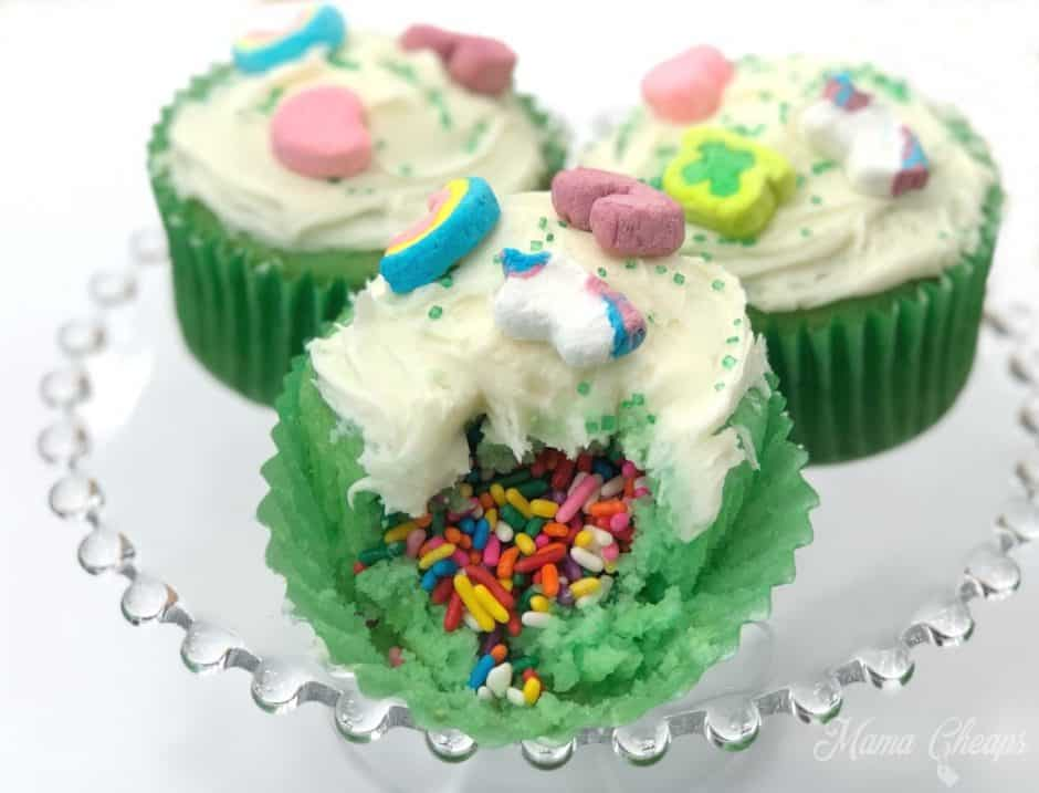 Lucky Charms Rainbow Surprise Cupcakes, three on a glass plate, one cut open to show sprinkles on the inside