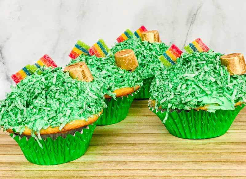 Pot of Gold Rainbow Cupcakes, white cupcakes topped with green frosting and coconut, and a gold rolo and rainbow candy