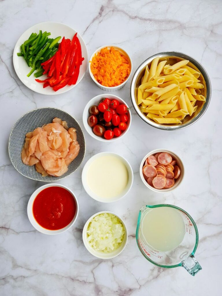 bowls of ingredients needed to make cajun chicken pasta