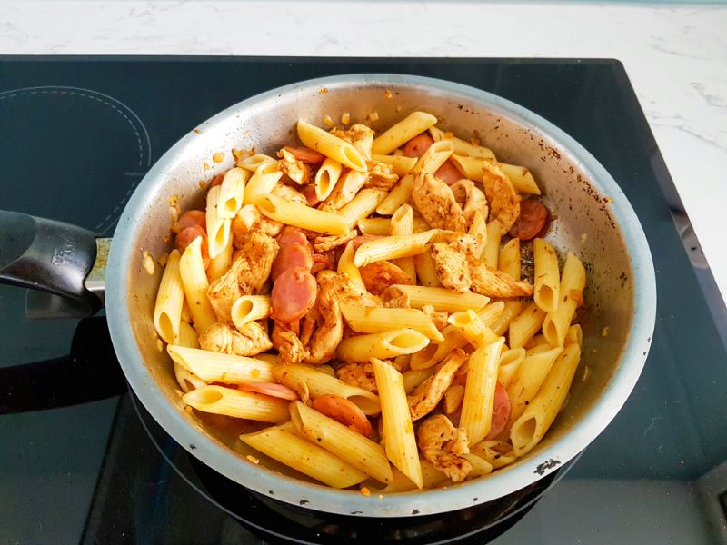 cooked pasta and water, smoked sausage, chicken pieces and onions cooking in a skillet