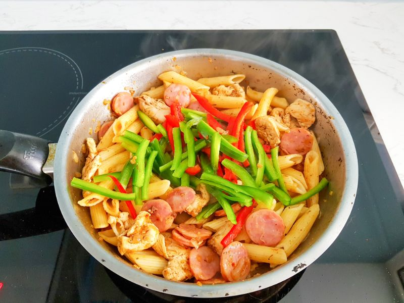 bell peppers, cooked pasta and water, smoked sausage, chicken pieces and onions cooking in a skillet