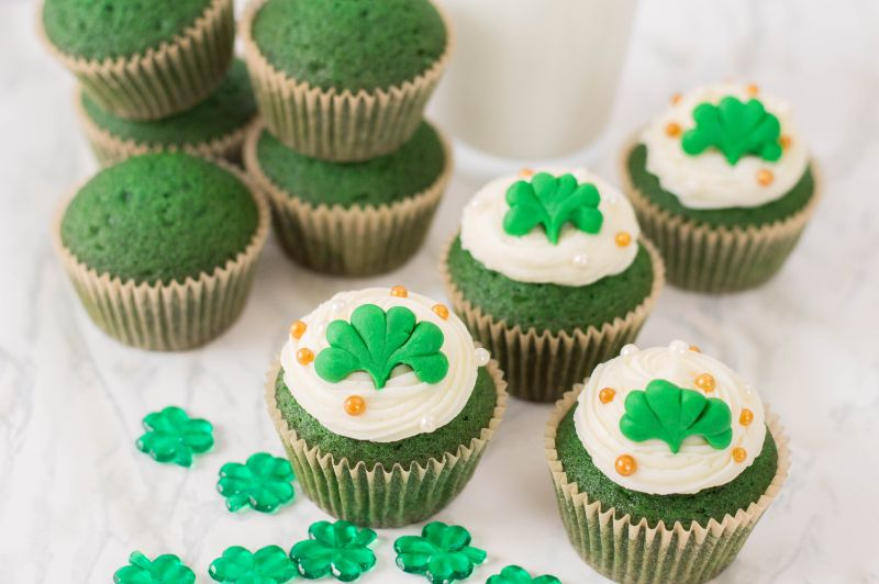 Homemade Green Velvet Cupcakes decorated for St. Patrick's Day next to shamrocks and a glass of milk on a white background
