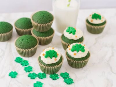 a dozen green velvet cupcakes with a glass of milk
