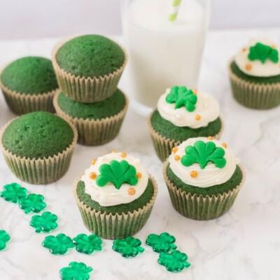 a dozen green velvet cupcakes with a glass of milk