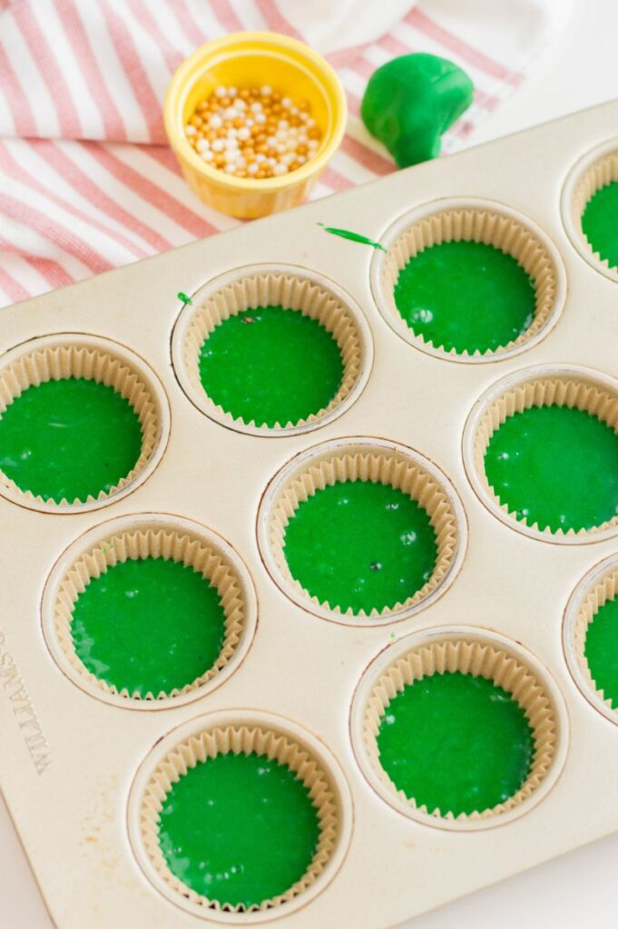 filling cupcake liners 2/3 full with green cupcake batter