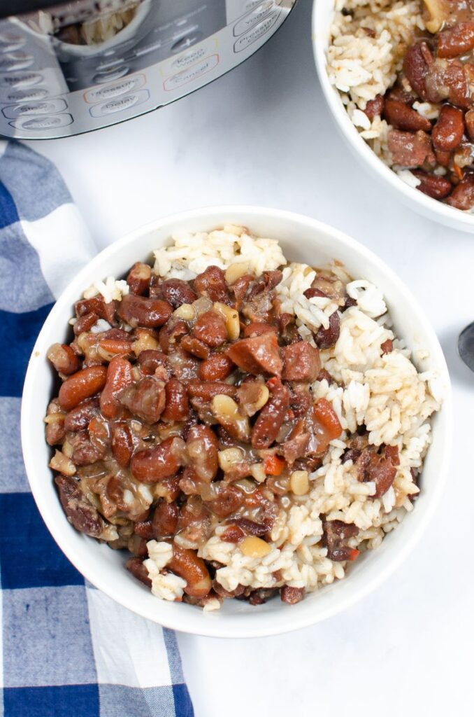 overhead view of Instant Pot Red Beans and Rice in a white bowl with another bowl in the background next to an instant pot