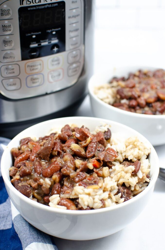 Instant Pot Red Beans and Rice in a white bowl with another bowl in the background next to an instant pot