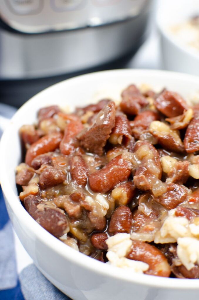 close up of Instant Pot Red Beans and Rice in a white bowl with another bowl in the background next to an instant pot