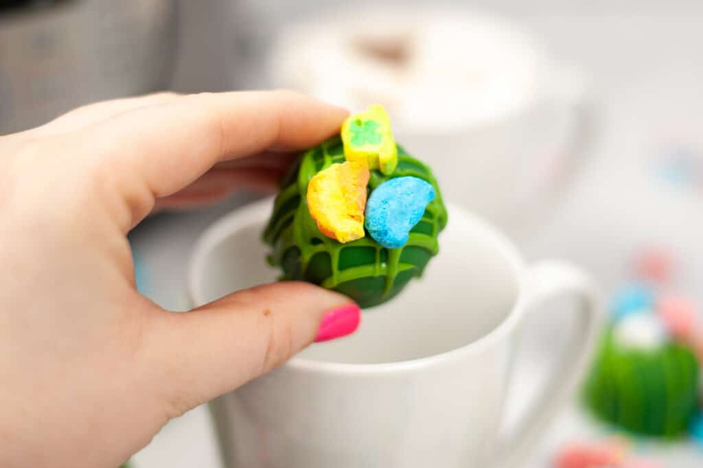 Instant Pot St. Patrick's Day Hot Cocoa Bombs being added to a mug