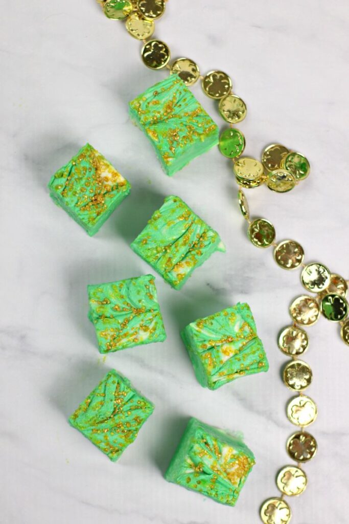 White Chocolate Mint Cheesecake Fudge on a counter next to a string of gold shamrocks