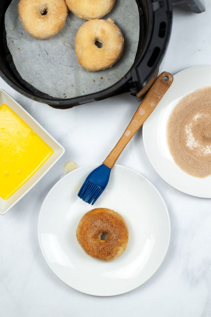 a coated donut on a white plate next to a blue pastry brush, next to a bowl of melted butter, plate of cinnamon sugar and donuts in an air fryer