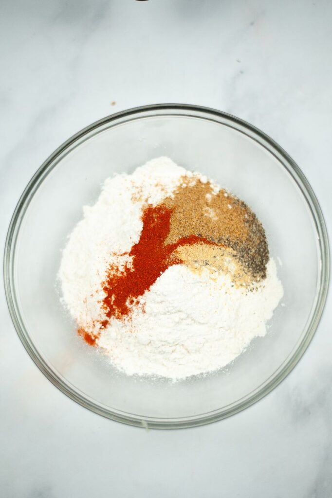 flour and seasonings in a glass bowl on a gray counter