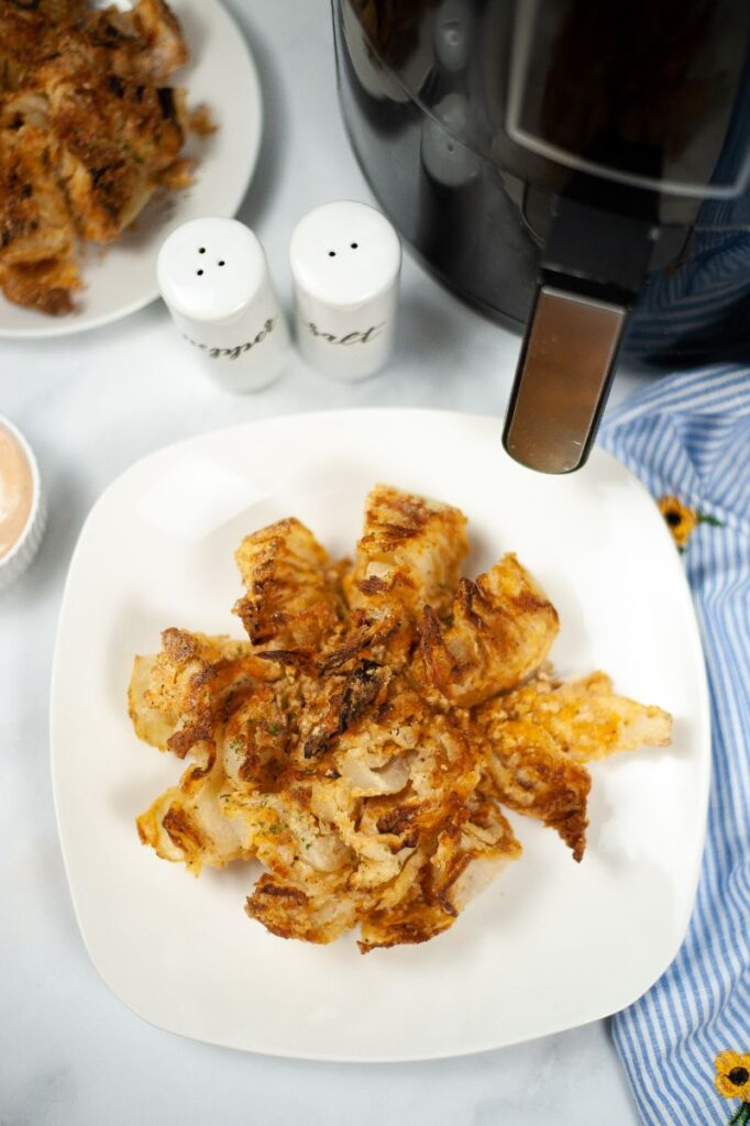 overhead view of a bloomin onion on a white plate with some white containers and an air fryer in the background
