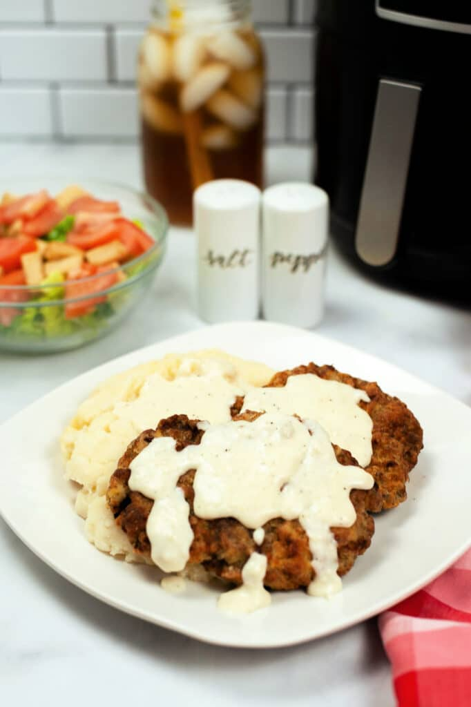 chicken fried steak with gravy on a white plate with a bowl of salad, salt and pepper shakers, a pitcher of tea, and an air fryer in the background