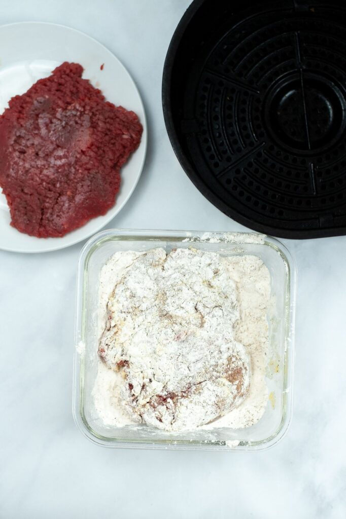 raw cube steak on a white plate next to an air fryer and raw cubed steak being coated with flour in a glass dish