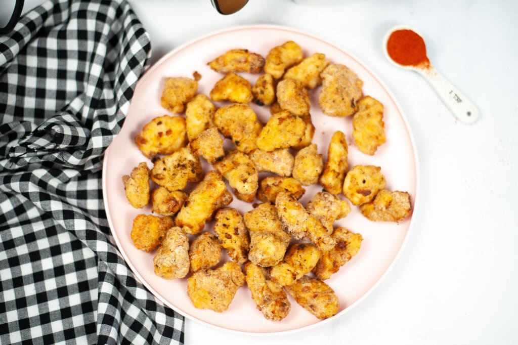 Air Fryer Copycat Chick Fil A Nuggets on table on white plate next to a black and white checkered cloth