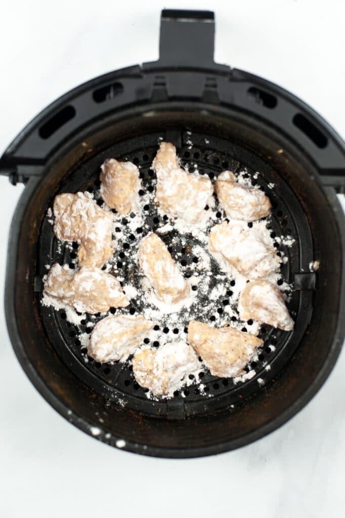 adding chicken into air fryer basket