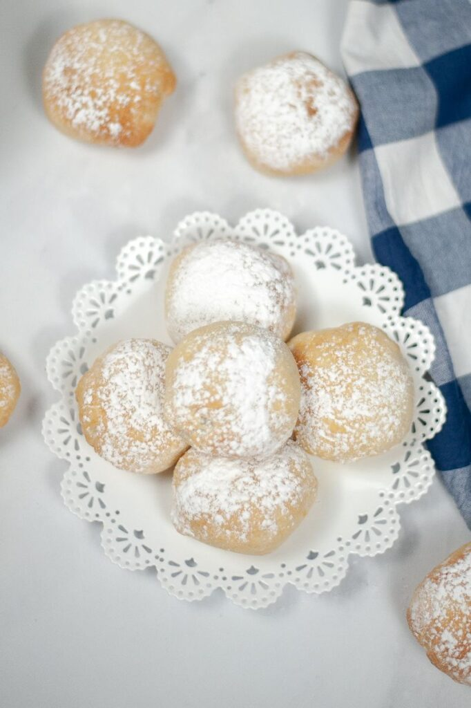 deep fried oreos on a white doily and white cloth next to a blue and white checkered cloth